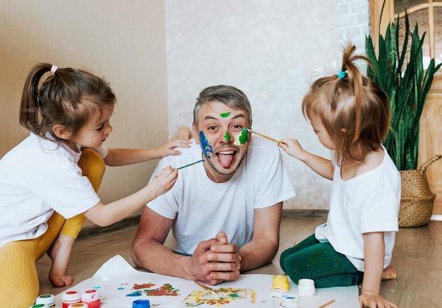 As crianças se divertem com o pai, as meninas desenham na pele do rosto de um homem com tintas coloridas, criatividade e imaginação, dia dos pais e o conceito de família
