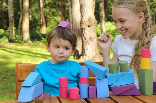 As crianças se divertem jogando cubos na natureza.