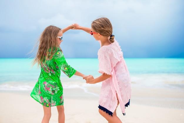 As crianças se divertem muito na praia tropical tocando juntos