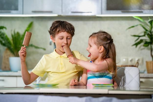 As crianças se sentam à mesa com sorvete no palito em cobertura de chocolate