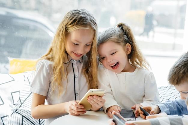 As crianças se sentam à mesa de um café e jogam celulares juntos. entretenimento moderno.