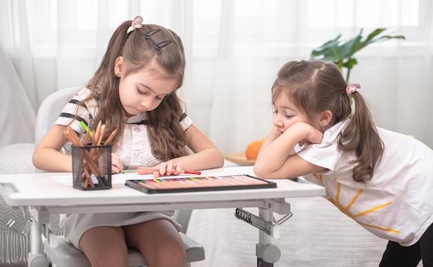 As crianças sentam à mesa e fazem a lição de casa. criança aprende em casa. educação escolar em casa.