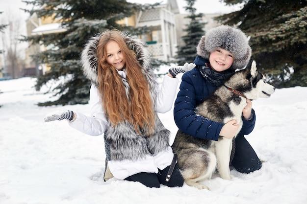 As crianças sentam-se na neve e acariciam cães husky