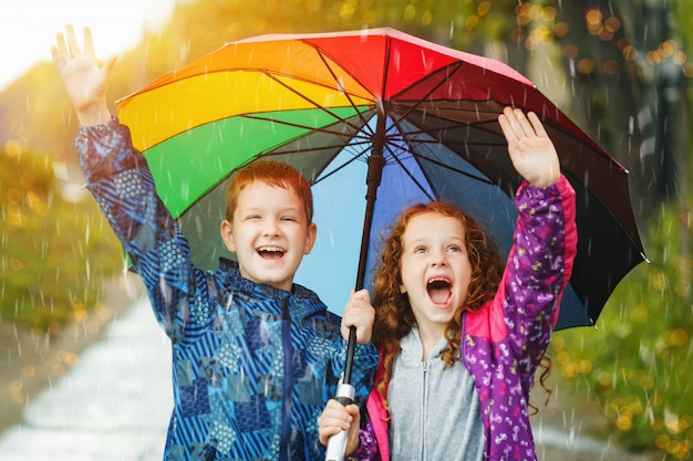 As crianças sob o guarda-chuva apreciam ao ar livre a chuva do outono.