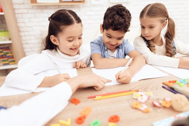 As crianças sorriem e escrevem em cadernos com uma caneta.