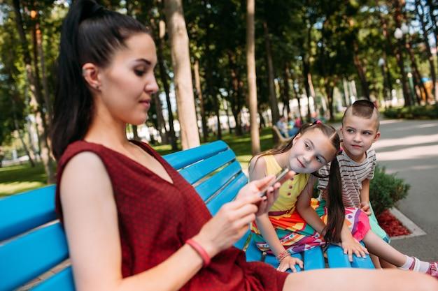 As crianças tentam atrair a atenção da mãe no parque. mãe usando telefone