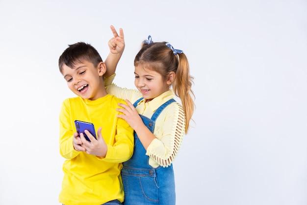 As crianças tiram selfies em um smartphone e colocam chifres.