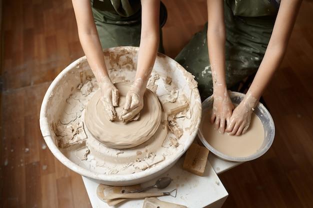 As crianças trabalham na roda de oleiro na oficina, com a vista superior nas mãos. aula de modelagem de argila na escola de arte. jovens mestres do artesanato popular, passatempo agradável, infância feliz