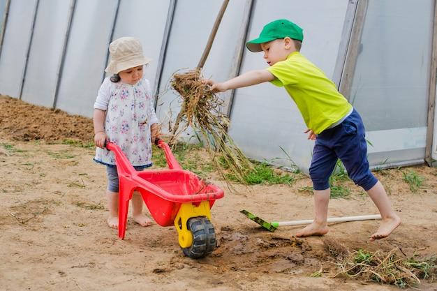 As crianças trabalham no jardim com uma pá e um carrinho de mão