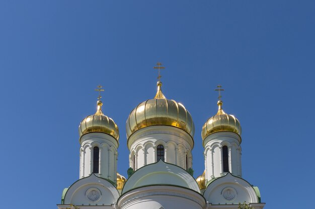 As cúpulas douradas da catedral de catarina, a catedral ortodoxa russa no fundo do céu azul brilhante.