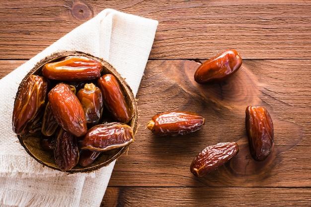 As datas secadas doces frutificam em uma bacia pequena no guardanapo na tabela de madeira. vista do topo