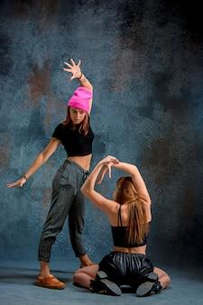 As duas garotas atraentes dançando twerk iat o azul