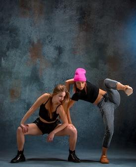 As duas garotas atraentes dançando twerk no estúdio