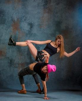 As duas garotas atraentes dançando twerk