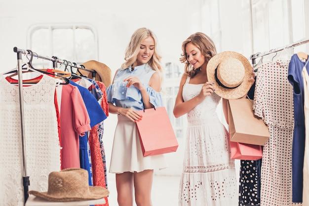 As duas garotas bonitas olhando vestidos e experimentando enquanto escolhem na loja