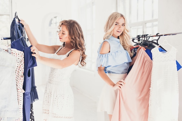 As duas jovens mulheres bonitas olhando vestidos e experimentá-lo enquanto escolhe na loja