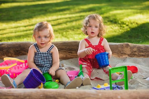 As duas meninas bebê de dois anos jogando brinquedos na areia contra a grama verde