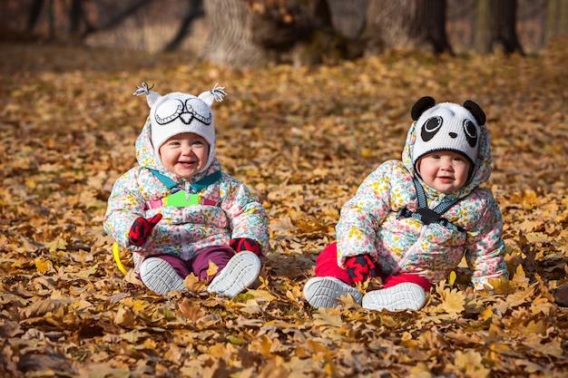 As duas meninas bebê sentado nas folhas de outono