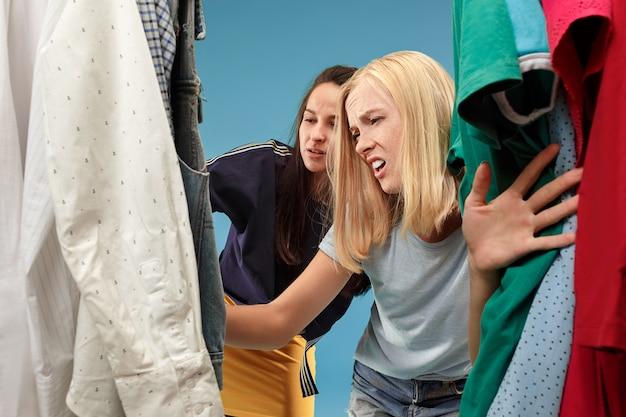 As duas meninas bonitas olhando vestidos e experimentá-lo enquanto escolhe na loja