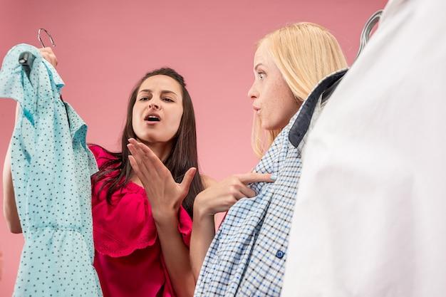 As duas meninas bonitas olhando vestidos e experimentando enquanto escolhem na loja