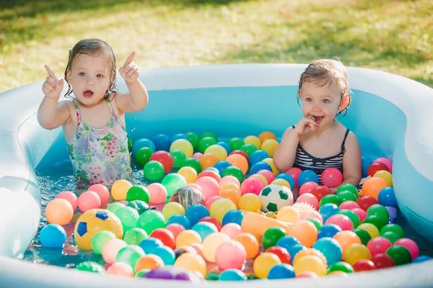 As duas meninas brincando com brinquedos na piscina inflável no dia ensolarado de verão