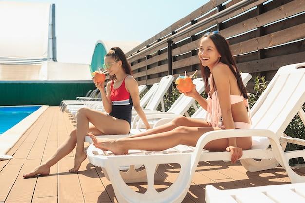 As duas meninas brincando e relaxando em uma piscina durante as férias de verão