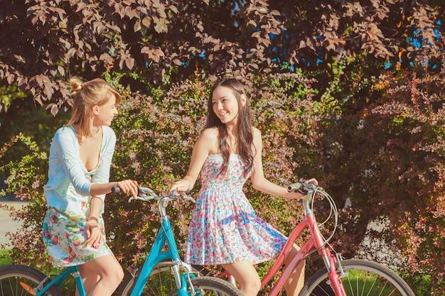 As duas meninas com bicicletas no parque