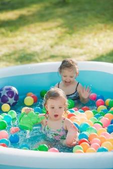 As duas meninas de dois anos de idade brincando com brinquedos na piscina inflável no dia ensolarado de verão