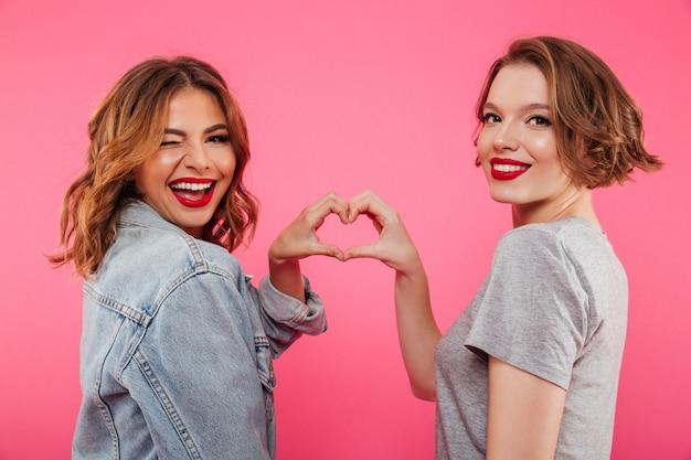 As duas mulheres alegres que abraçam mostrando o coração amam o gesto.