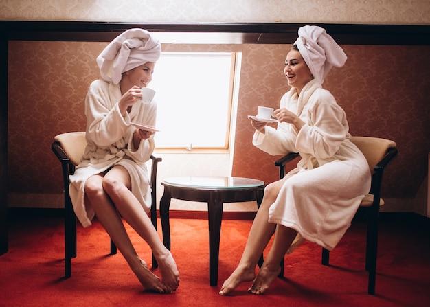 As elegantes irmãs tomando café pela manhã