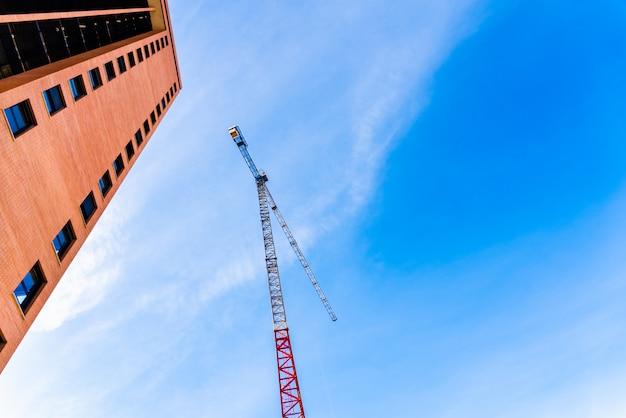 As empresas de construção residencial instalam grandes guindastes para criar casas e são vendidas por especialistas do setor imobiliário.