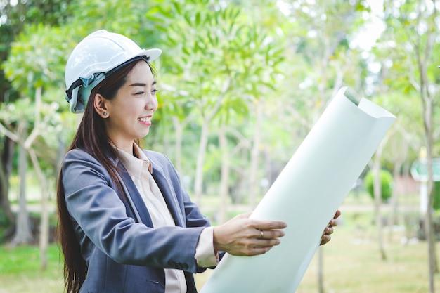 As engenheiras usam capacetes de segurança brancos, seguram o papel para a construção civil.
