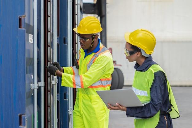 As equipes de logística do armazém usam laptop para verificar produtos na caixa contêineres no transporte de contêineres de carga