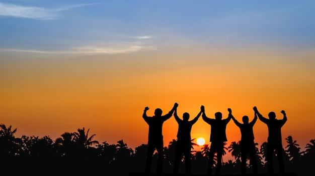 As equipes que estão dispostas a compartilhar o sucesso estão unidas, de mãos dadas, olhando para o pôr do sol.
