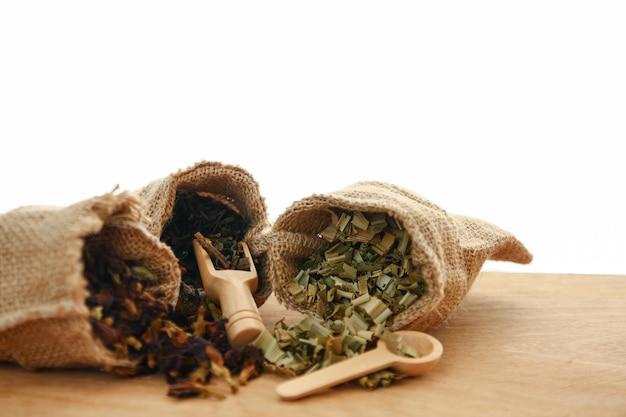 As ervas asiáticas estão em sacos marrons e colheres de pau, colocadas no chão de madeira. fundo branco