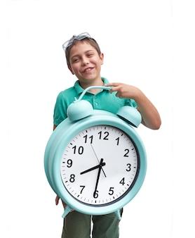 As escolas começam muito cedo. menino com grande despertador gren.