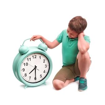 As escolas começam muito cedo. menino com grande despertador.