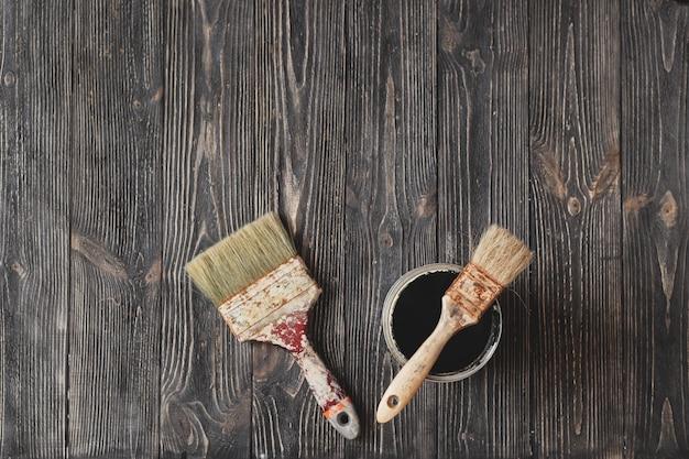 As escovas velhas e as latas da pintura enegrecem na tabela envelhecida.