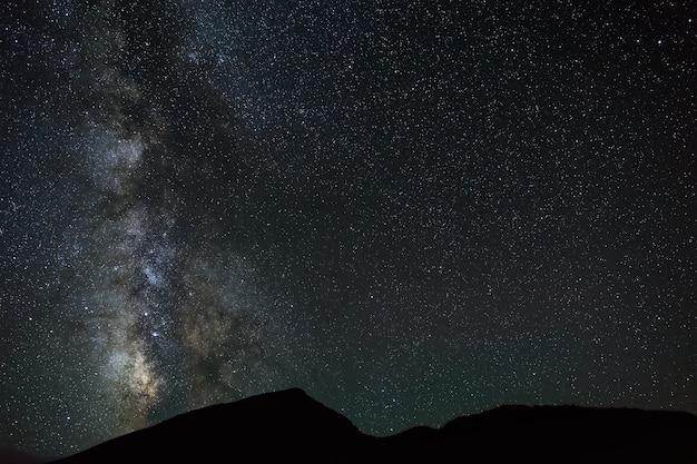 As estrelas brilhantes da via láctea no céu noturno sobre as montanhas do norte do cáucaso.