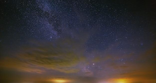 As estrelas da via láctea com nuvens no céu noturno
