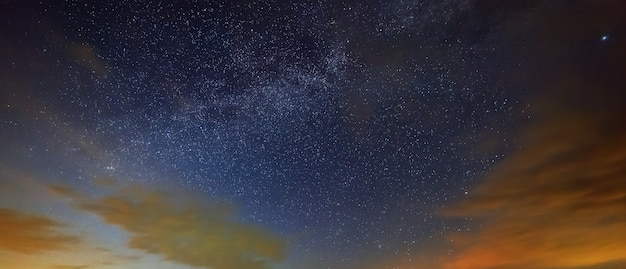 As estrelas da via láctea com nuvens no céu noturno.