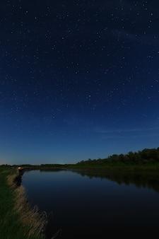 As estrelas no céu noturno são refletidas no rio