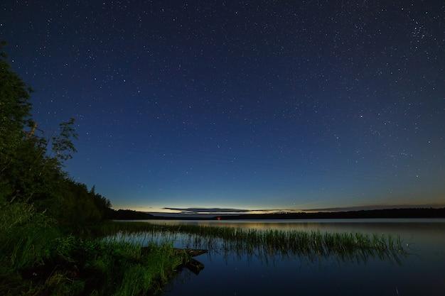 As estrelas no céu noturno sobre o rio