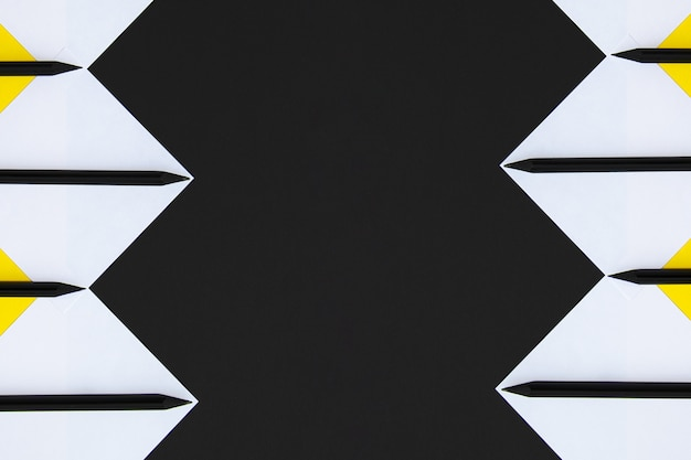 As etiquetas brancas e amarelas com lápis pretos alinharam com um teste padrão geométrico em um fundo preto.