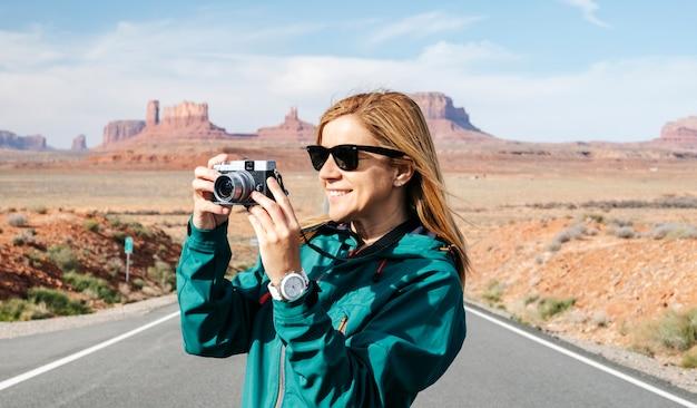 As excursões de uma mulher tiram uma foto com a câmera na famosa estrada do deserto de monument valley, em utah, eua.