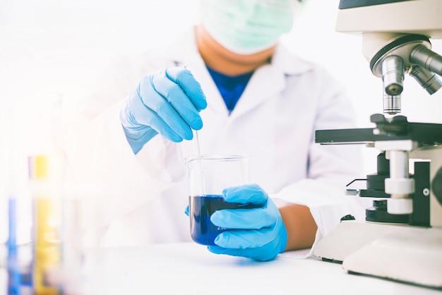 As experiências do equipamento e da ciência lubrificam o cientista de derramamento com a pesquisa de fatura azul do tubo de ensaio no laboratório.