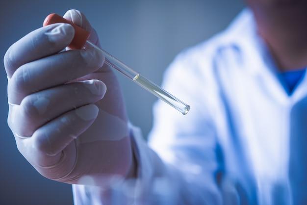 As experiências do equipamento e da ciência lubrificam o cientista de derramamento com pesquisa de fatura verde do tubo de ensaio no laboratório.