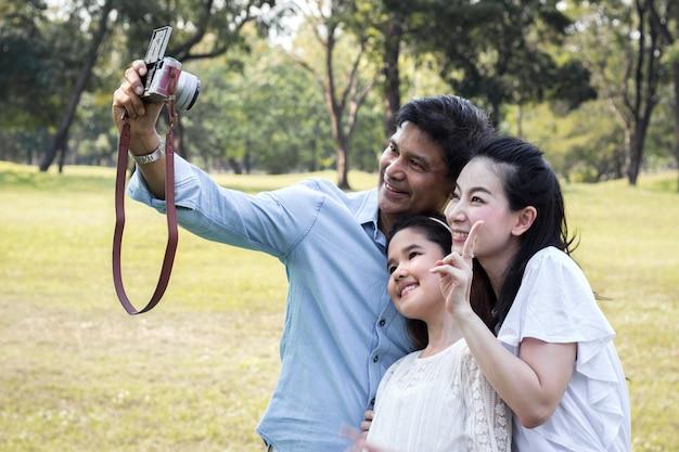 As famílias asiáticas estão tirando fotos de família em um parque público.