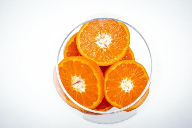 As fatias de laranja de frutas em um vaso de vidro