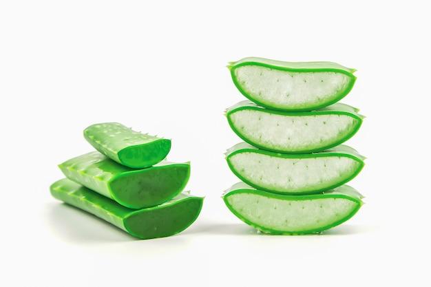 As fatias de planta fresca de vera do aloés empilhadas e o aloés vera perseguem ou saem com o isolado deixando cair da água no branco.